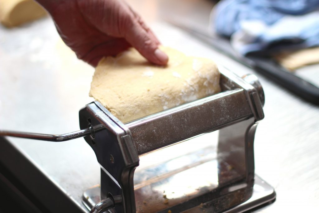 Dough being fed into pasta machine