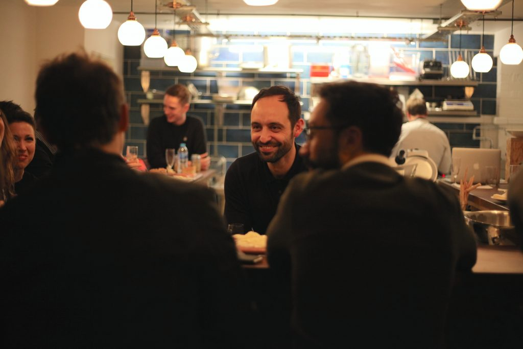 David Toscano, owner of Cin Cin, chatting with guests at the bar