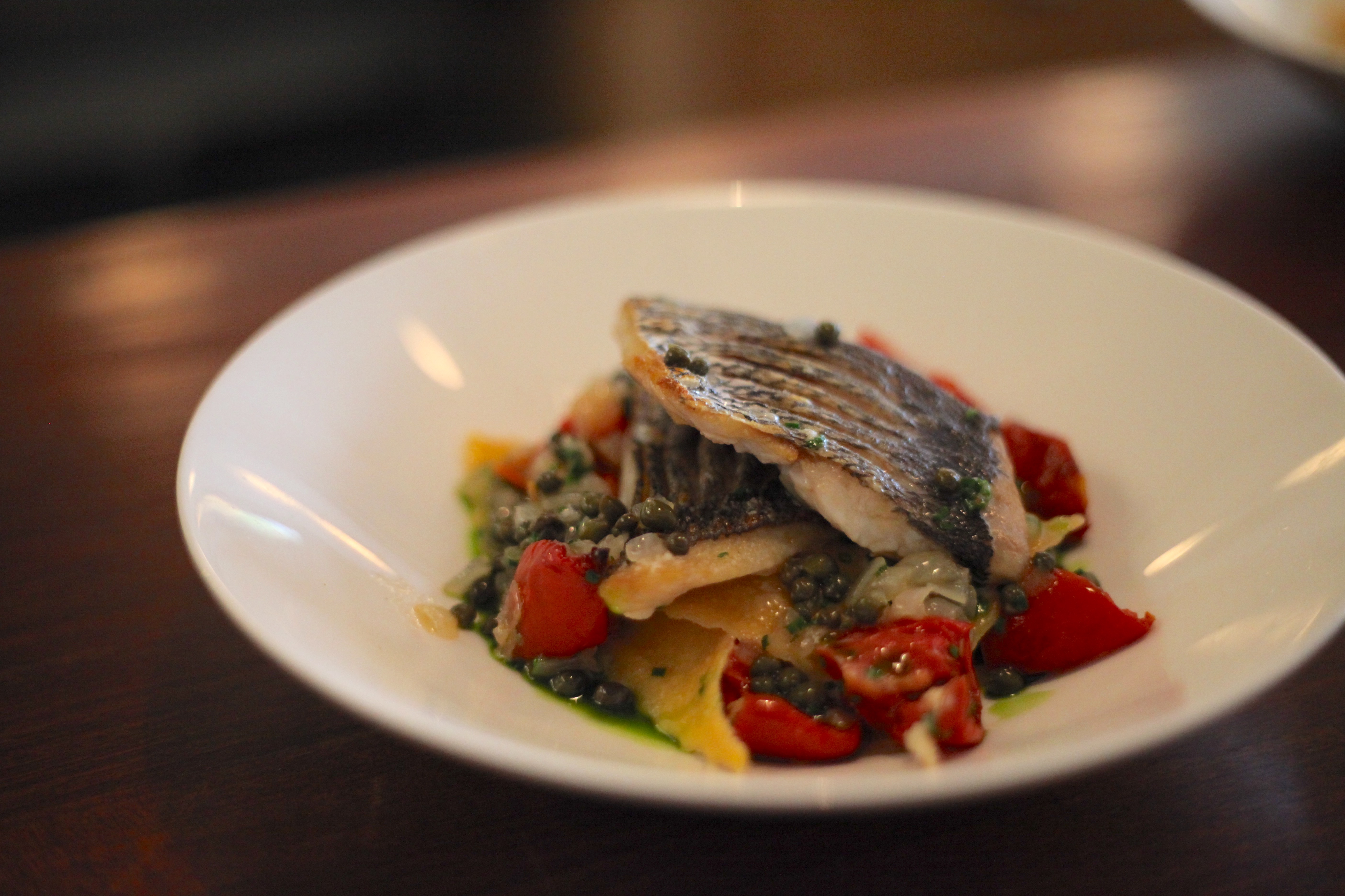 Bowl of fazzoletti with black bream, capers, tomatoes, basil and stracciatella