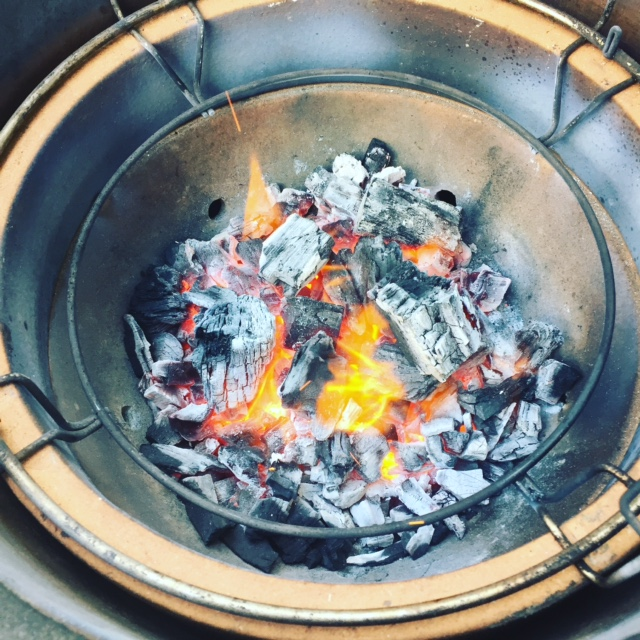 BBQ bowl filled with coals on fire
